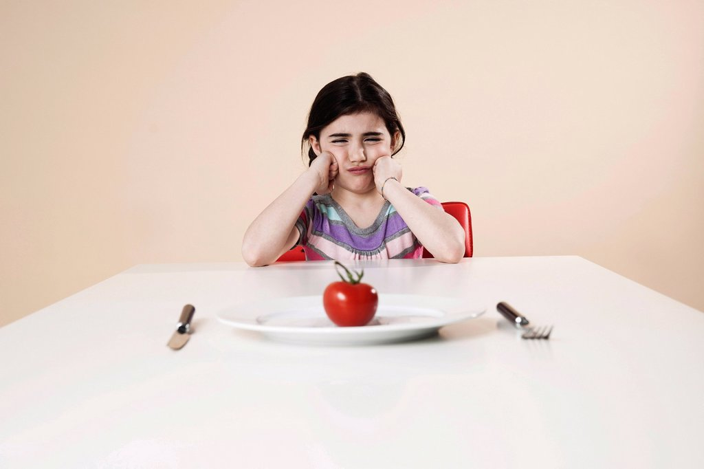 Girl looking with disgust at the tomato on her plate : Stock Photo