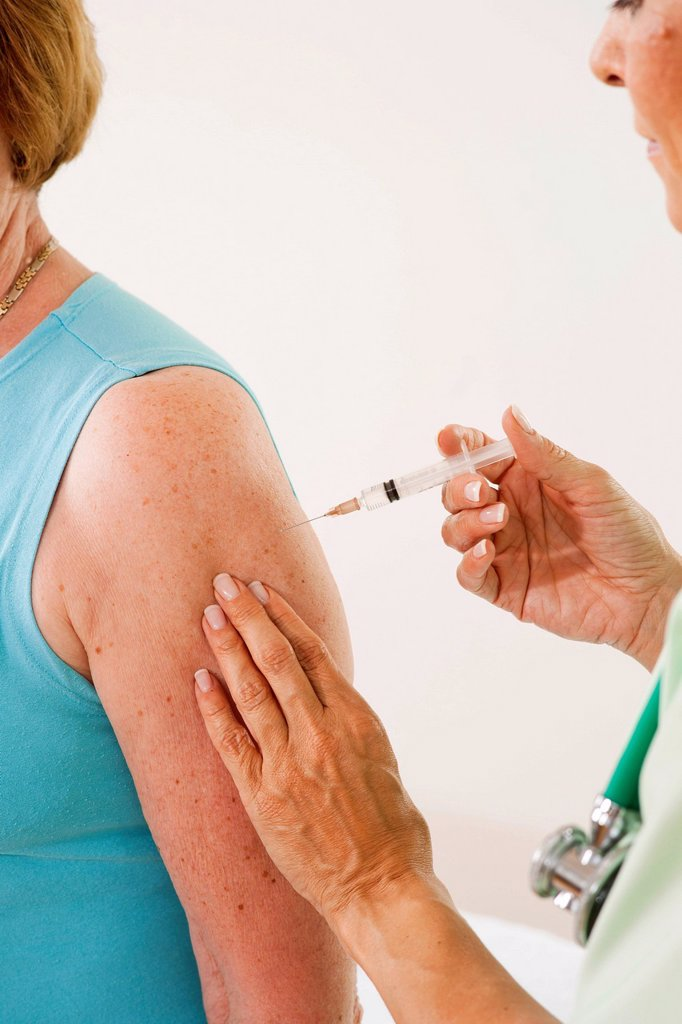 Patient receiving an injection from her doctor, vaccination : Stock Photo