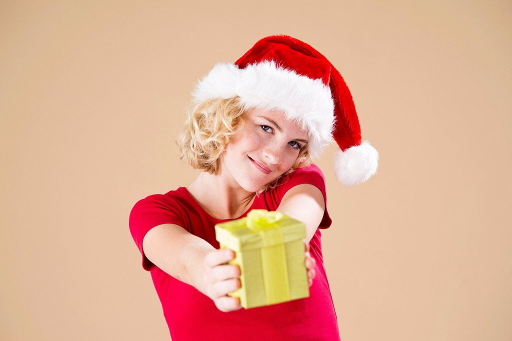 Smiling blond young woman wearing a Santa hat and presenting a gift : Stock Photo