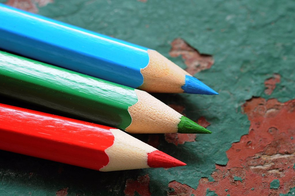 Stock Photo: 1848R-748026 Wooden coloured pencils, red, green and blue on an old wooden board