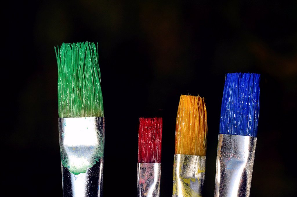 Bristle brushes with green, red, yellow and blue paint : Stock Photo