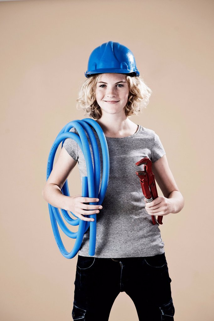 Stock Photo: 1848R-753673 Girl wearing a hard hat and holding a pipe wrench
