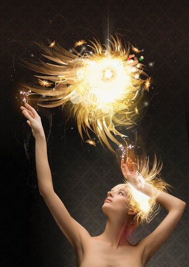 Stock Photo: 1849-1020 Woman reaching up to abstract glowing ball