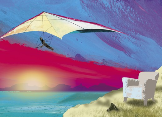 Armchair on cliff with hang-glider soaring over ocean : Stock Photo
