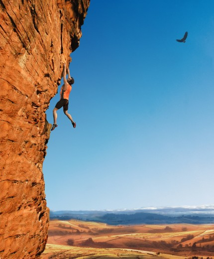 Stock Photo: 1849-802 Rock climber dangling from cliff wall