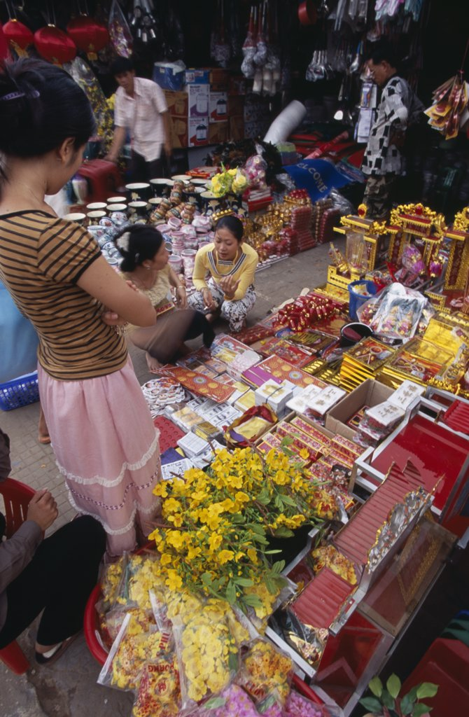 Cambodia, Siem Reap, Display Of Various Religious Goods For Sale In The Old Market During Chinese New Year With Customers Buying Goods : Stock Photo