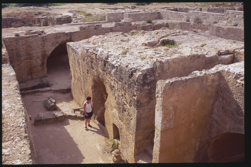 Stock Photo: 1850-11116 Cyprus, Paphos, Tomb Of The Kings With Tourist Looking Through Entrance.