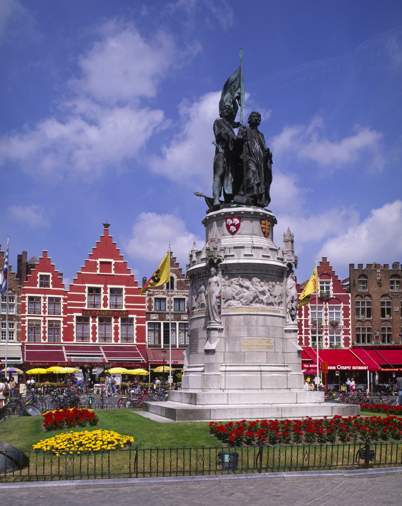 Belgium, West Flanders, Bruges, Statue Of Jan Breydel And Pieter De Coninck In The Market Place. Row Of Cafes And Restaurants Behind. : Stock Photo