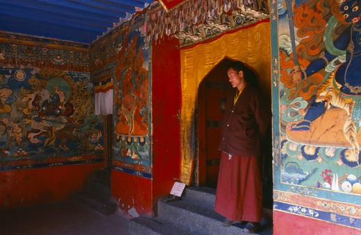 Tibet, Sakya, Monk Standing In A Doorway With Brightly Painted Religious Scenes And Deities Around Him. : Stock Photo