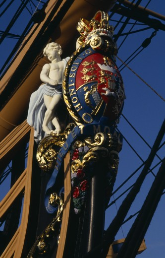 Stock Photo: 1850-1286 England, Hampshire, Portsmouth, Admiral Lord Nelson'S Hms Victory. Detail Of Elaborate Figurehead Of Two Cupids Supporting The Royal Coat Of Arms And Royal Crown. The Arms Bear The Norman French Inscription Of The Order Of The Garter Honi Soit Qui Mal Y Pense Which Means-Shame To Him Who Evil Thinks