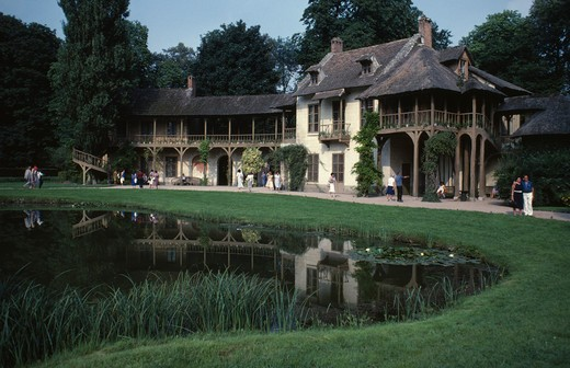 Stock Photo: 1850-1309 France, Ile De France, Paris, 'Versailles.  The Queens Cottage In The Hamlet, Exterior With Tourist Visitors Reflected In Pond.'
