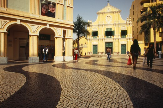 Stock Photo: 1850-13226 China, Macau, Church Of St Dominic.  Exterior With People Walking Across Mosaic Tiled Area In The Foreground.