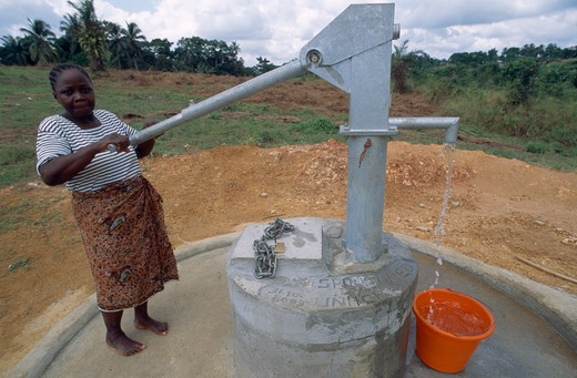 Stock Photo: 1850-13259 Liberia   , Margibi, Kakata, Young Woman Pumping Clean Water From Unhcr Supplied Water Pump.