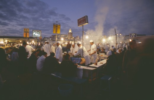 Stock Photo: 1850-13880 Morocco, Marrakesh, Djemaa El Fna. Food Vendors Serving Up Food To Hungry Customers Seated Around Them At Dusk