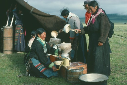 Stock Photo: 1850-14009 Tibet, People, Tibetan Nomad Women On The High Grasslands With Cream Seperator Brought By Travelling Salesman.