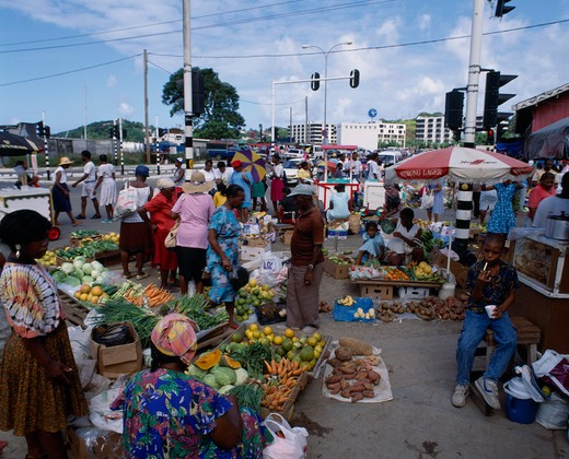 West Indies, St Lucia, Castries, 'Fruit And  Vegetable Street Market. Pumpkins, Carrots, Cabbage, Yams, Spring Onions, Bananas, Oranges Near Street With Traffic Lights And Ice-Cream Vendor In Background. ' : Stock Photo