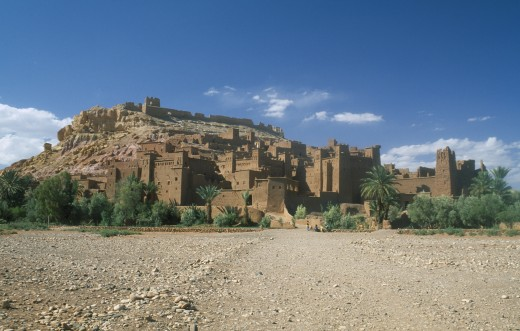 Stock Photo: 1850-14459 Morocco, Ait Benhaddou, Kasbah Famous For Appearing In Films Such As Jesus Of Nazareth And Lawrence Of Arabia.  Exterior Walls With Small Group Of People In Foreground.