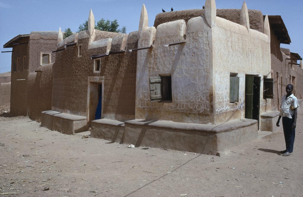 Stock Photo: 1850-14526 Nigeria, Kano, Traditional Hausa Dwelling And Mud Architecture With Man Standing Outside.