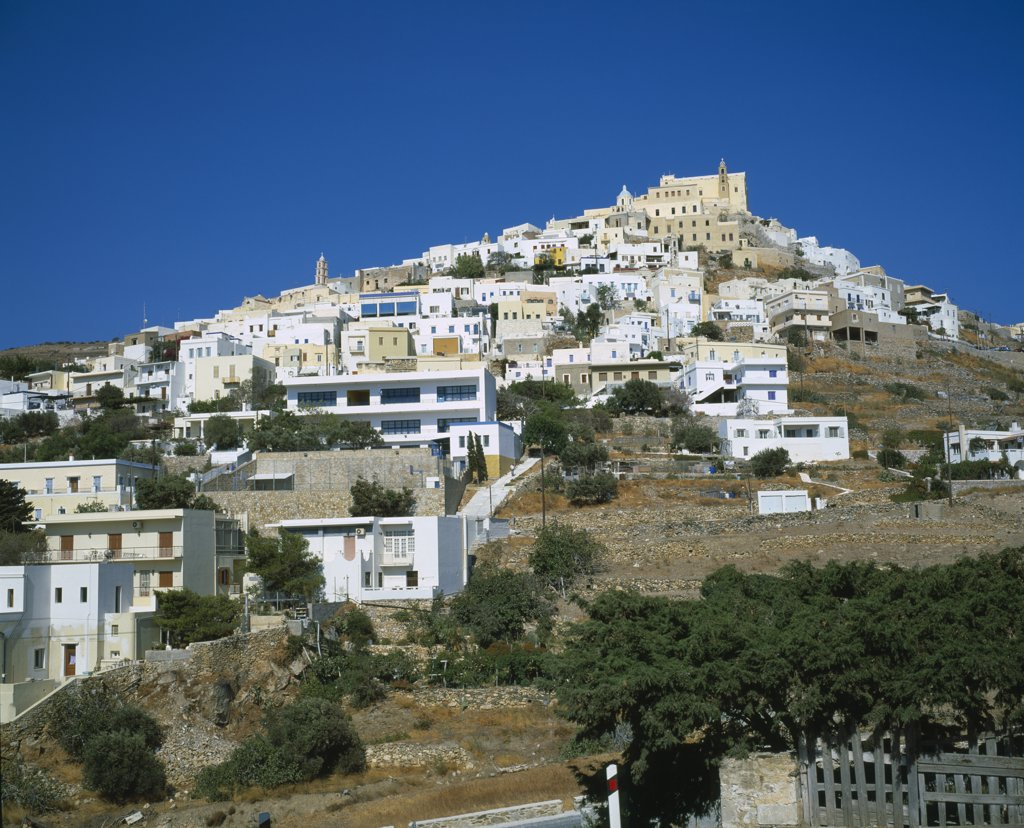 Stock Photo: 1850-14767 Greece, Cyclades Islands, Syros, Ermoupolis. The Catholic Quater Of Ano Syros And Church Of Ag. Yiorgios. Houses Covering Mountain Side With Trees And A Wall In The Foreground.