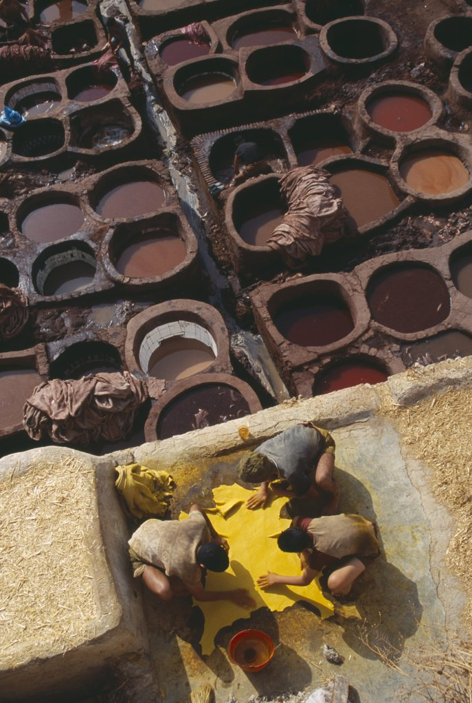 Stock Photo: 1850-15084 Morocco, Fes, Chouwara Tanneries.  Men Working At The Tanner?S Pits With Coloured Dyes.