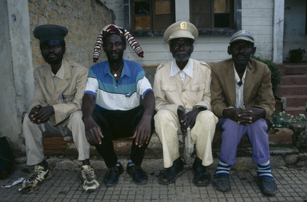 Angola, Malange, Four Malange Chiefs Seated And Wearing Different Hats. : Stock Photo