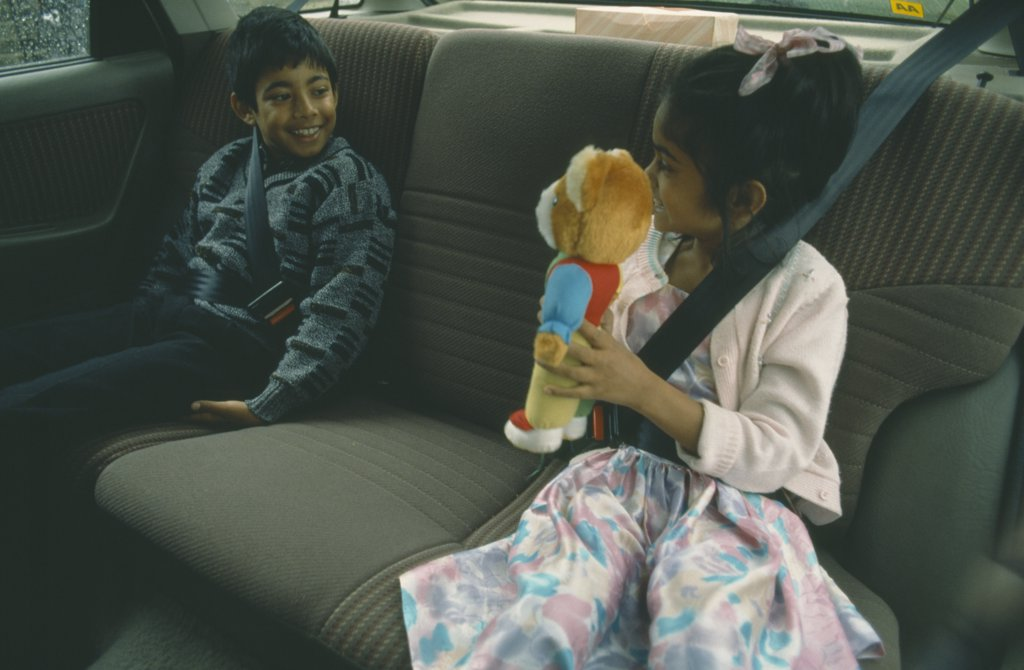 England, London, Children, Two Bengali Children In Back Seat Of Car Wearing Seat Belts.  Young Girl Showing Teddy Bear To Boy. : Stock Photo