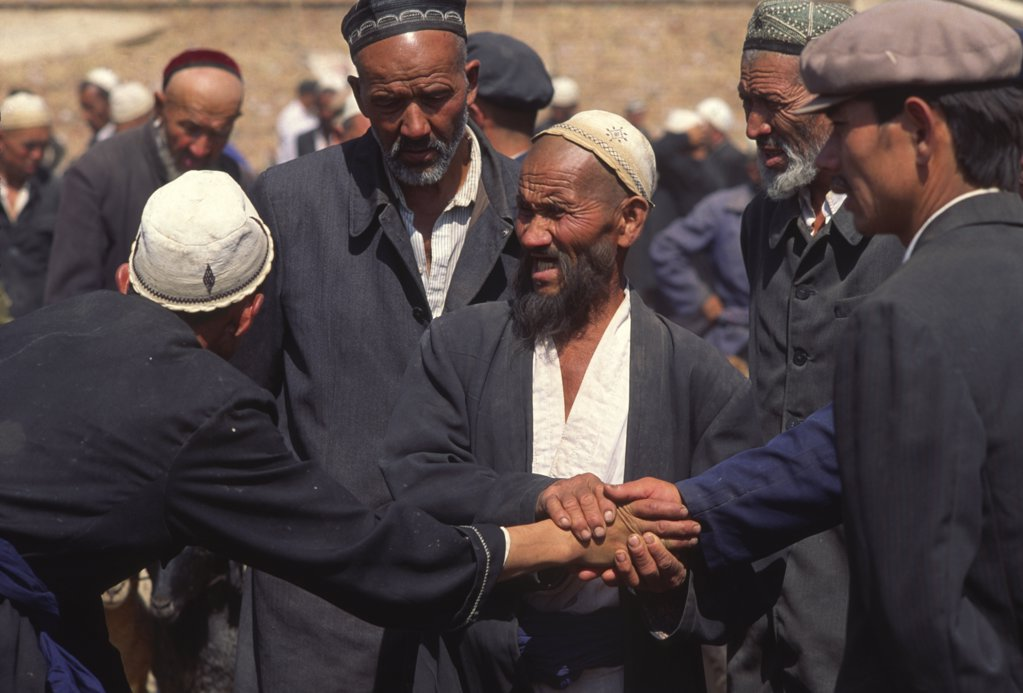 Stock Photo: 1850-15976 China, Xinjiang Province, Kashgar, Tajik Men Touching Hands Striking A Deal With Central Man Acting As A Witness