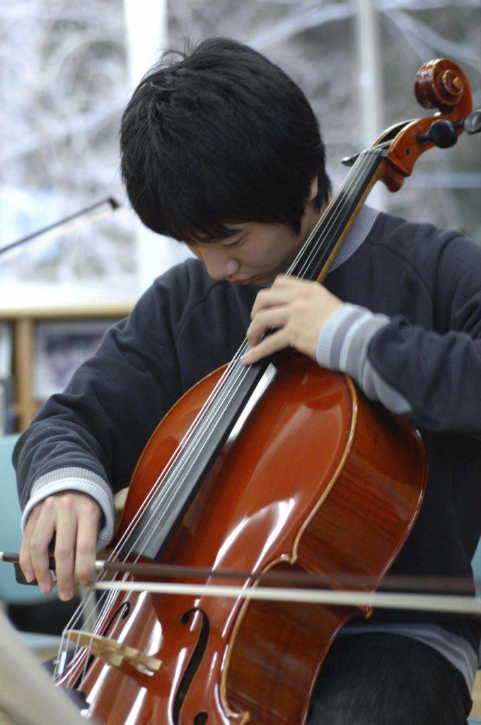 Japan, Chiba, Yokaichiba, Teenage Boy Playing Cello As Member Of United Freedom Orchestra : Stock Photo
