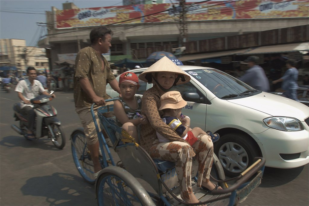 Stock Photo: 1850-16290 Vietnam, South, Ho Chi Minh City, People Riding A Cyclo Down A Busy Street With A Car Beside Them