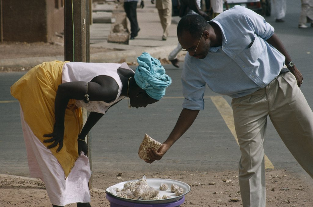 Gambia, Markets, Woman Selling Cashew Nuts To A Man Along The Road Side : Stock Photo