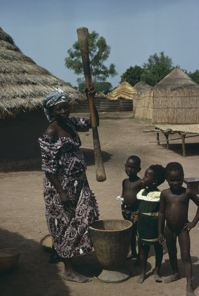 Gambia, Agriculture, Woman Pounding Grain In Village With Children Gathered Around Her : Stock Photo