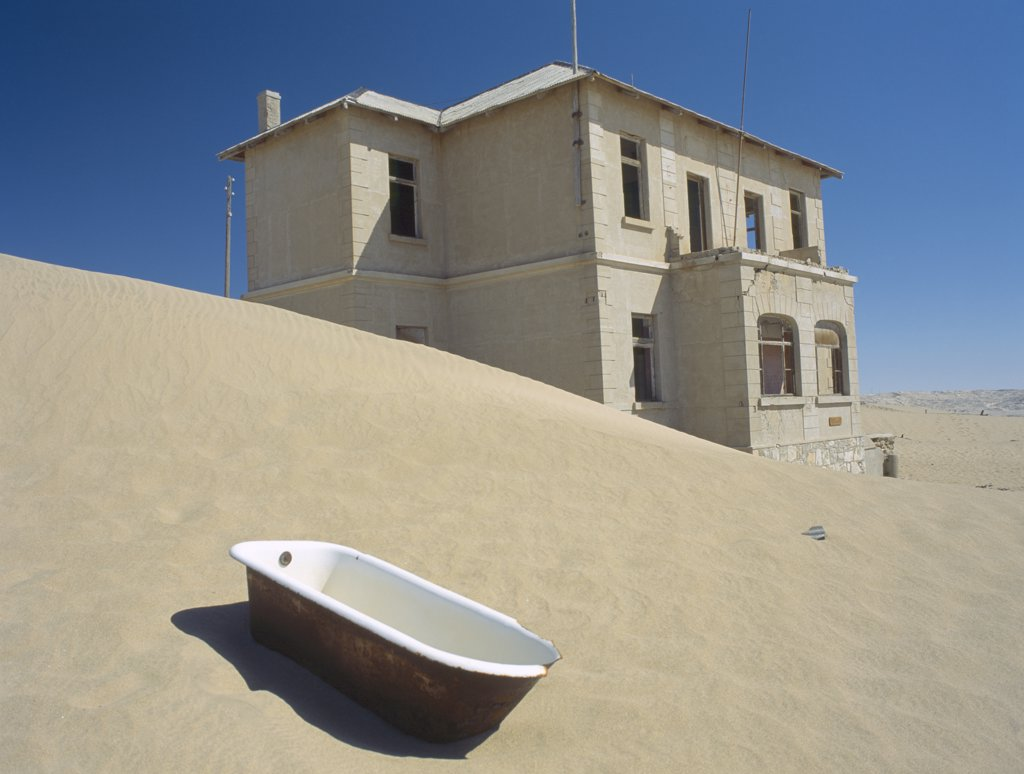 Stock Photo: 1850-16622 Namibia, Kolmanskop, A House With A Bath Tub In The Foreground  With Desert Sands Encroaching.