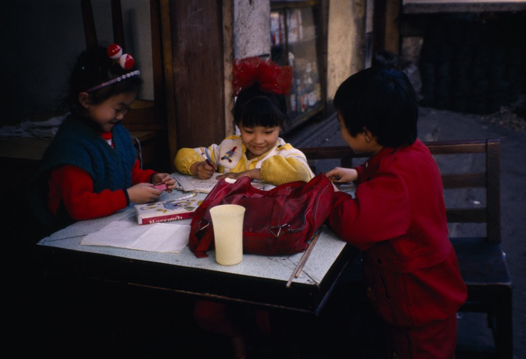 China, Guiyang, Children Doing Homework Outside House. : Stock Photo