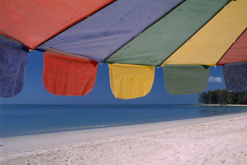 Thailand, North Phuket, Naiyang Beach, Close Up Of A Multi Coloured Parasol On The Sandy Beach. : Stock Photo