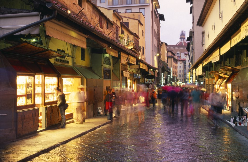 Italy, Tuscany, Florence, 'Street Scene At Dusk With Shop Fronts Lining Ponte Vecchio, Crowds In Blurred Movement And Lights Reflected On Wet Paving.' : Stock Photo
