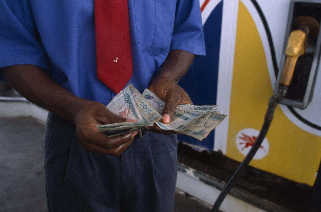 Stock Photo: 1850-17099 Ghana, Money, Ghanaian Currency.  Counting Cedi Bank Notes At A Petrol Station.