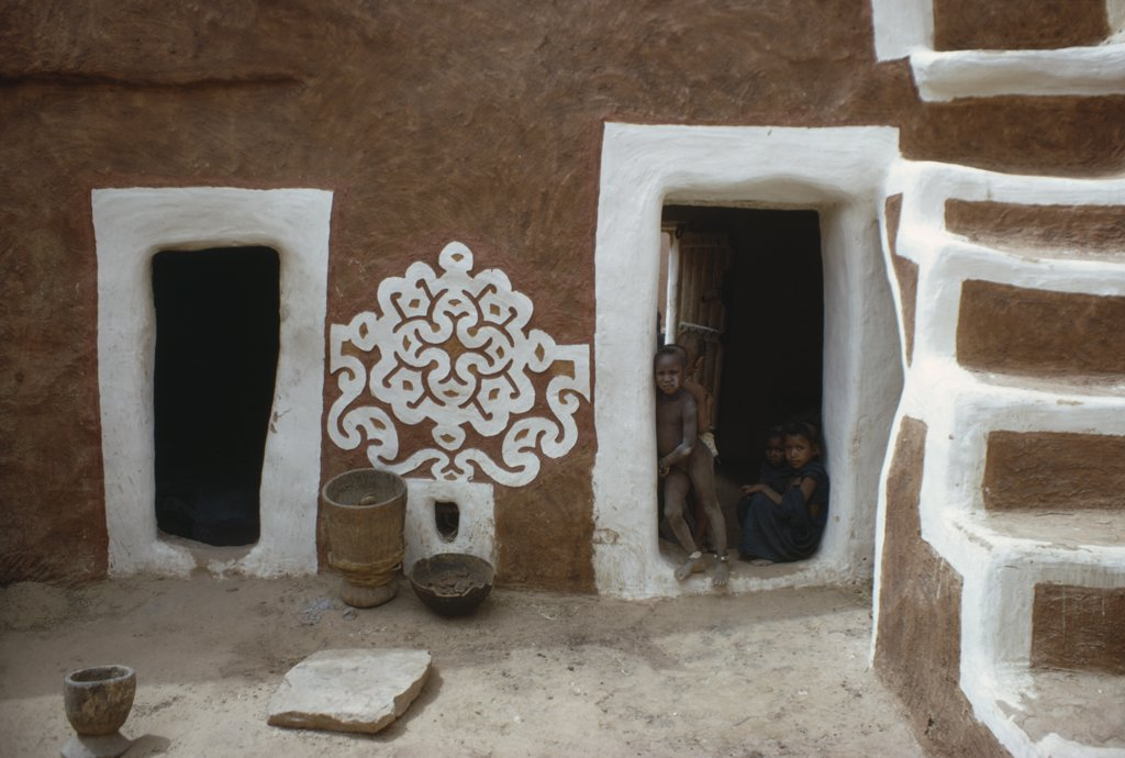 Stock Photo: 1850-17367 Mauritania, Oualata, Traditional Mud Architecture Decorated With Bas Relief Motif Of Applied Gypsum  White And Red Clay.  Children Framed In Open Doorway With White Surround.