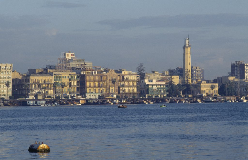Stock Photo: 1850-17578 Egypt, Port Said, City On Coast Where The Suez Canal Meets The Mediterranean And Founded In 1859 To House Canal Workers.  City And Suez Canal At Dusk.