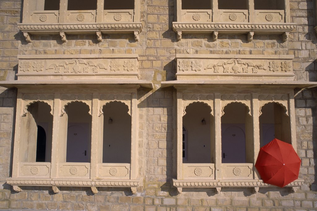 Stock Photo: 1850-17921 India, Rajasthan, Jaisalmer, Hotel Himmatgarth Palace Exterior With Detail Of Windows And A Red Unbreller