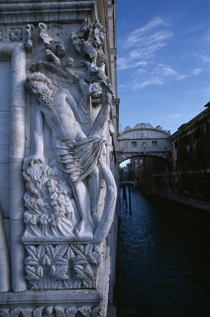 Italy, Veneto, Venice, The Doges Palace. Relief Carving Of The Drunkenness Of Noah Or The Vine Angle On The Corner Of Building Beside The Bridge Of Sighs With Water Below : Stock Photo