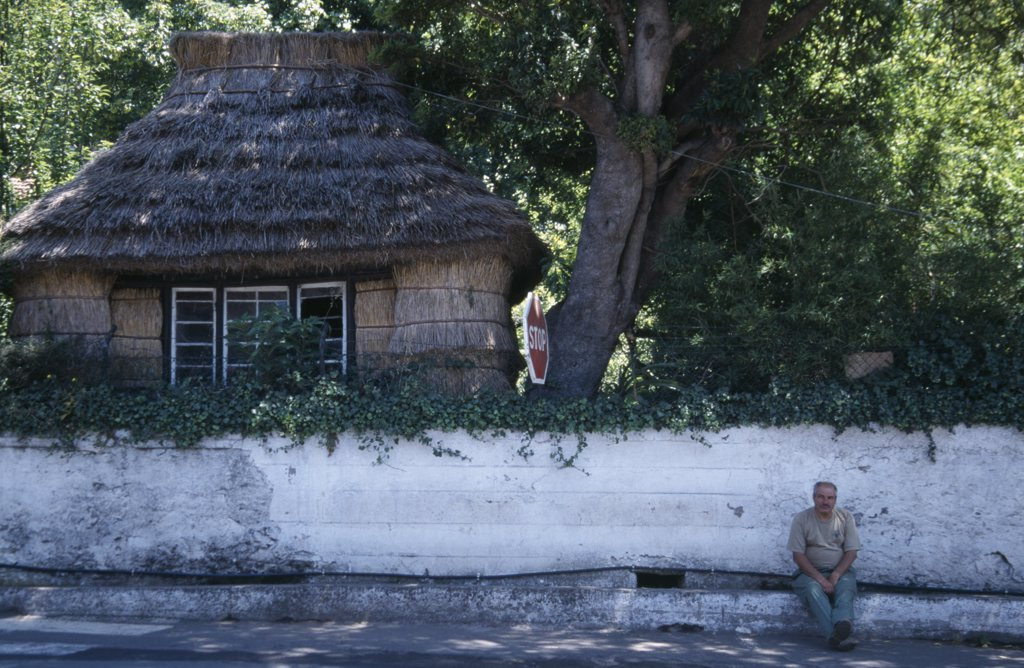 Portugal, Madeira, Camacha, Traditional Thatched Cottage Beside The Larg Do Achada The Central Square With A Man Sat On The Pavement Next To A White Wall : Stock Photo
