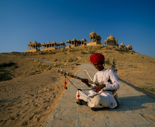 India, Rajasthan, Jaisalmer, Musician Wearing A Red Turban Sitting Cross-Legged On The Ground With Old Buildings On Top Of The Hill Behind Him : Stock Photo