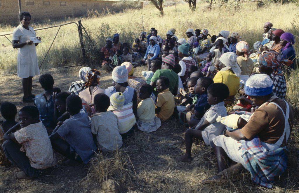 Zimbabwe, People, Family Planning Association Education Officer And Distributor Talking To Women On Farming Compound. : Stock Photo