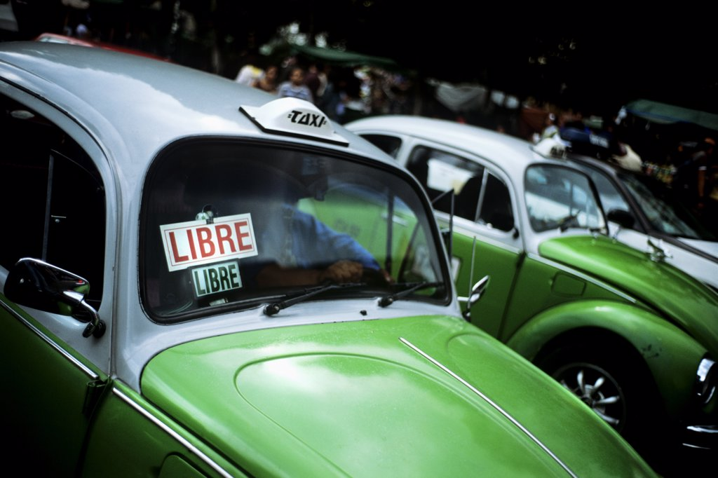 Stock Photo: 1850-18386 Mexico, Mexico City, Down Town Mexico City On The North Side Of The Zocolo Sits A Line Of The World Famous Green Beatle Taxis. All Taxis In Mexico City Are Of This Design And Being The Middle Of The Day Business Seems To Be A Little Slow. In The Background One Can Make Out The Blurs Of A Bustling City Centre Whereas In The Foreground Are Quietly Parked A Whole Line Of Taxis. Each One Almost Identical. Painted Halfway In Traditional Mexican Green With Their Top Halves In White. On Top Of Each Roo