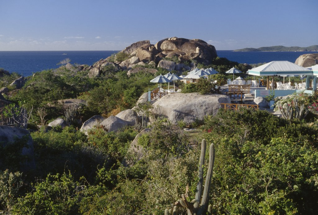 British Virgin Islands, Virgin Gorda, The Baths. Granite Boulders Amongst Plants And Vegetation With Chairs And Sun Shades From A Restaurants Open Air Verandah In The Middle. The Ocean Seen In The Distance : Stock Photo