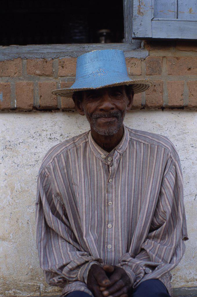 Madagascar, Ihosy, Portrait Of An Elderly Man Sitting Against A Wall Wearing A Blue Straw Hat : Stock Photo