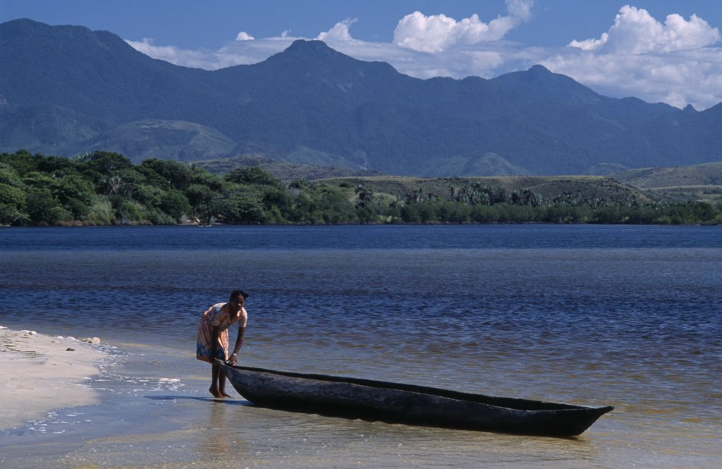 Stock Photo: 1850-18710 Madagascar, Fort Dauphin, Lokaro, A Woman Standing At The Waters Edge Of A Sandy Beach About To Push Her Pirogue Back Into The Water To Return To Her Village With Mountains In The Distance