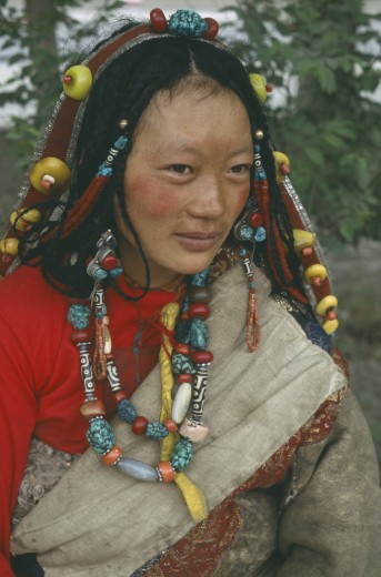 China, Qinghai, Golmud, Tibetan Woman In Traditional Clothes Wearing Beads In Hair And Around Neck : Stock Photo