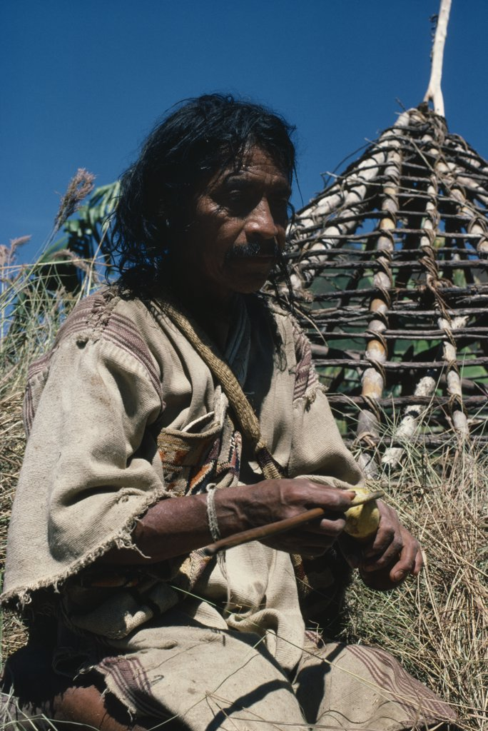 Stock Photo: 1850-18874 Colombia, Sierra Nevada De Santa Marta, San Antonio, 'Mama/Priest Valencia Takes A ''Coca Break'' - Taking Lime Powder From His Poporo/Gourd To Put Into Wad Of Coca Leaves In His Mouth - Whilst Thatching The Roof Of His House Wearing Traditional Thick Woven Cotton Manta/Cloak Indigenous Tribes American Northern Caribbean Slopes Of Sierra  '