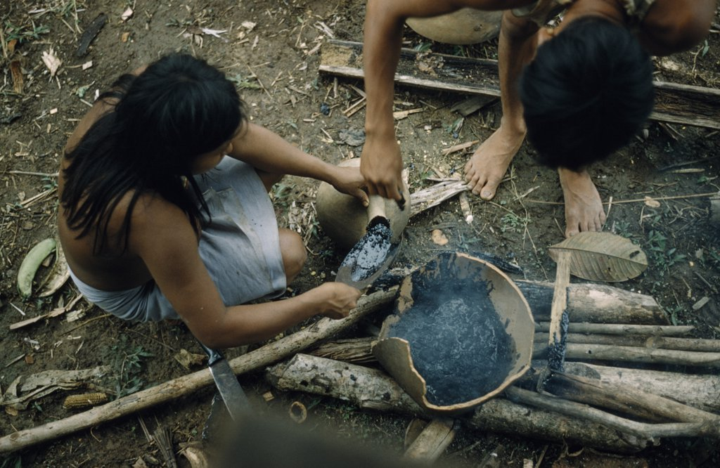 Stock Photo: 1850-18916 Colombia, Choco Region, Noanama Tribe, Woman Pouring ?Breo? / Melted Beeswax Into A Fired ?Cantaro? / Clay Water Pot Which Will Now Be Watertight